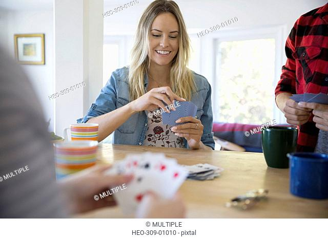 Smiling young woman playing cards with friends