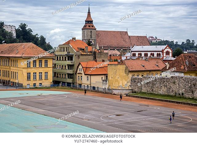 Black Church (Romanian - Biserica Neagra) in Brasov, Romania. Sports arena of High School on foreground