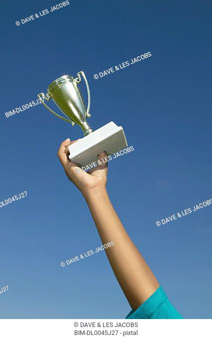 Boy's arm holding trophy in air