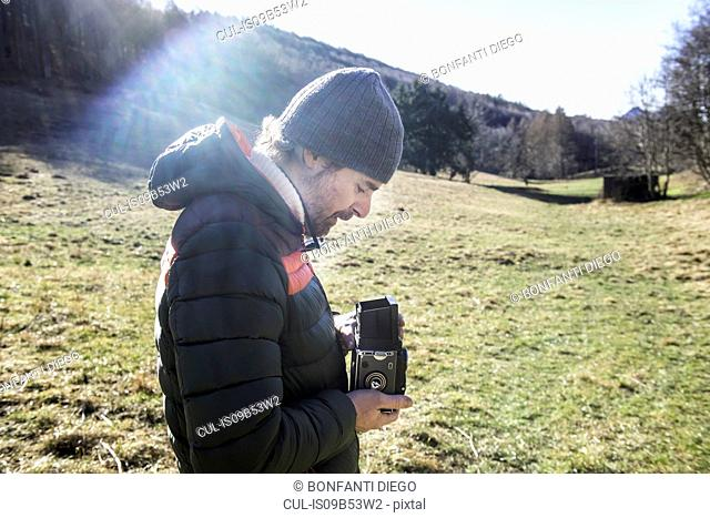 Man in rural setting, taking photograph with medium format camera, Italy