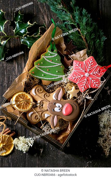 Christmas Handmade patterned gingerbreads as Christmas tree, reindeer Rudolph and snowflake shapes in wooden box over old wooden table