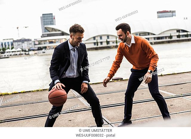 Two colleagues playing basketball after work
