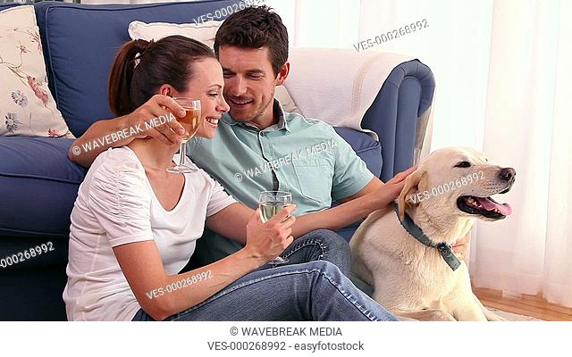 Happy couple sitting floor drinking wine with their pet dog