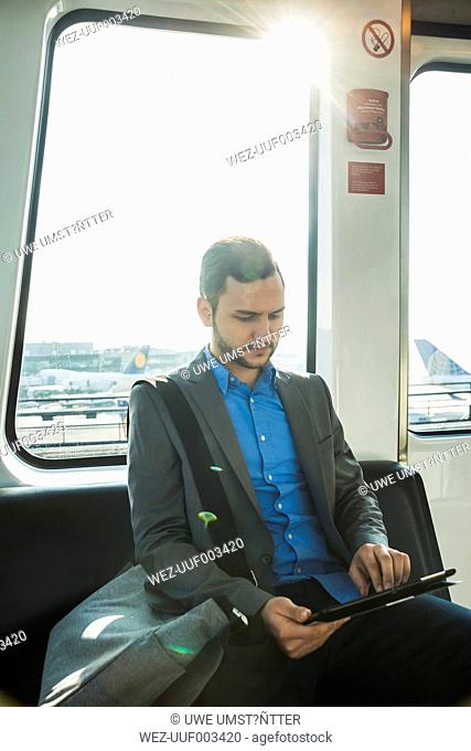 Germany, Frankfurt, young businessman in bus at the airport