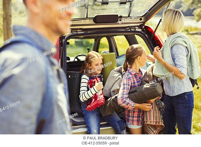 Family unloading camping equipment from car