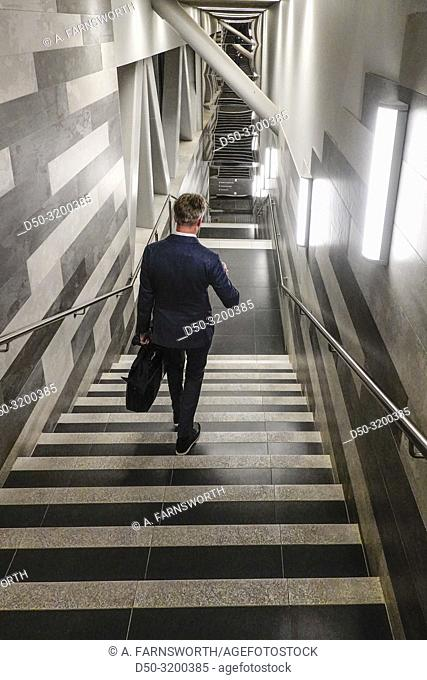 A man descends a public staircase with a cup of coffee. Stockholm, Sweden