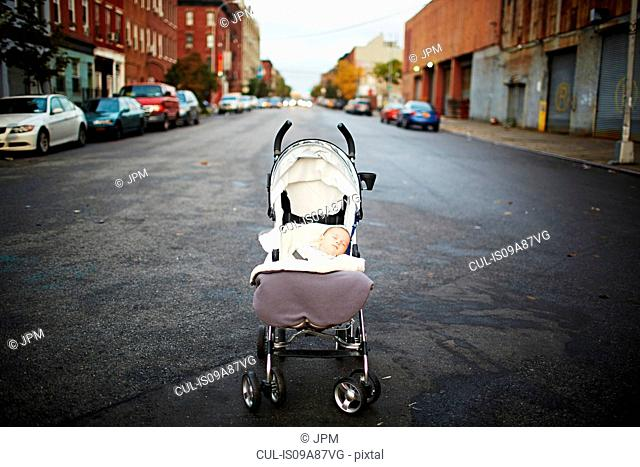 Baby boy asleep in push chair in middle of street