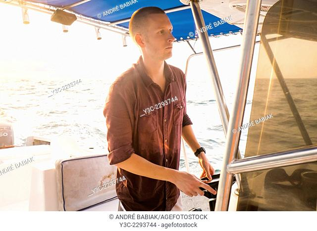 A young caucasian man, casually dressed, is steering a fishing boat at sea