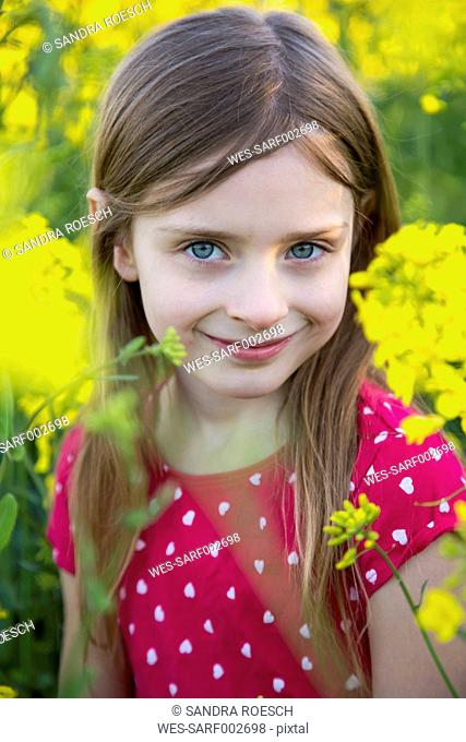 Portrait of smiling girl in a rape field