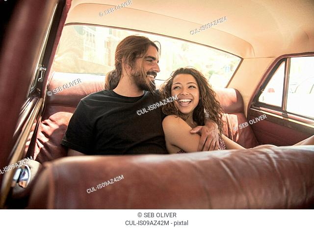 Young couple on road trip in vintage car back seat, Cape Town, South Africa