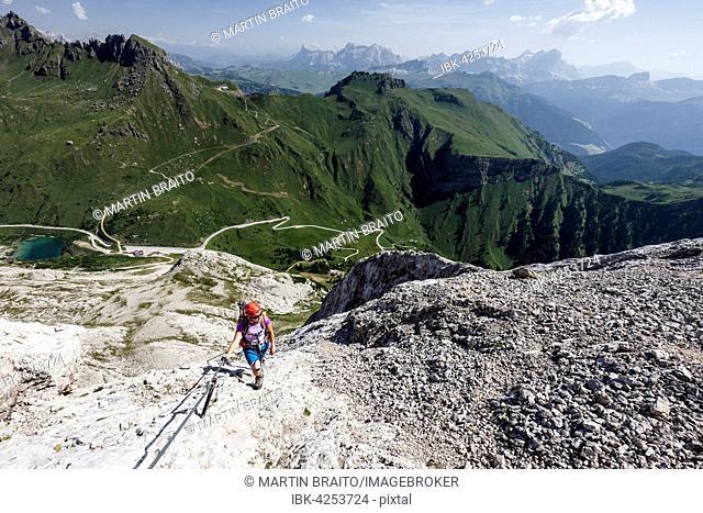 Mountaineer ascending to the Punta Serauta on the Via Ferrata Eterna in Marmolada, below the Fedaia Pass, behind the Heiligkreuzkofel