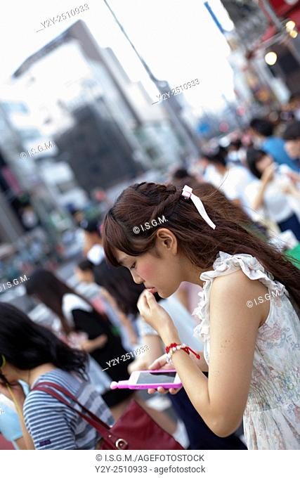 Girl with phone in Takeshita street at Tokyo, Japan