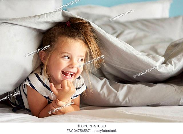 Cheerful girl hiding under the sheets