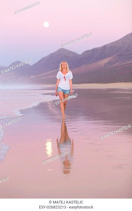 Woman walking on sandy beach in dusk leaving footprints in the sand. Beach, travel, concept. Copy space. Vertical composition
