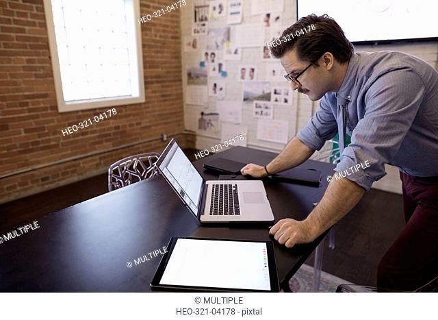 Male designer working at laptop in conference room
