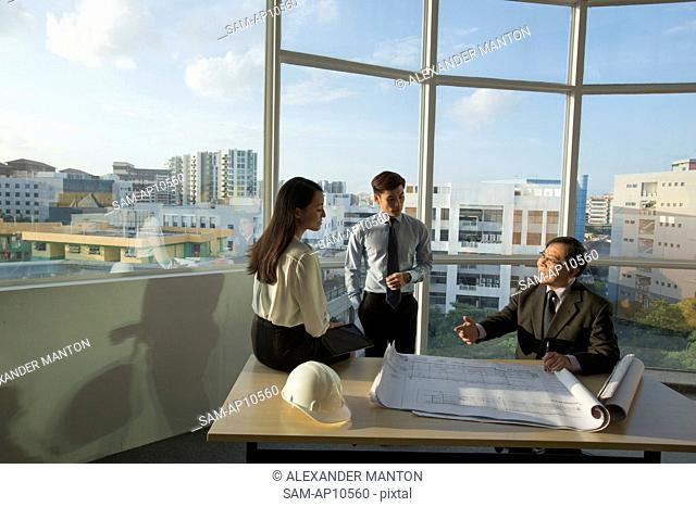 Singapore, Three people discussing architectural plans in office