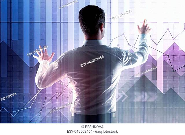 Back view of young businessman managing creative forex chart interface. Fund management and finance concept. Double exposure