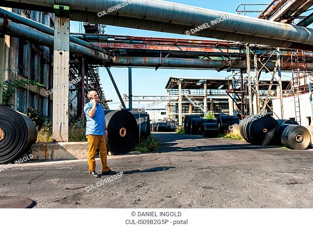Man using mobile in yard of castor wheel production factory, Ballenstedt, Germany