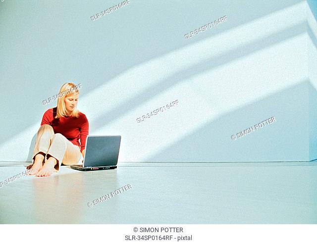 Businesswoman using laptop on floor