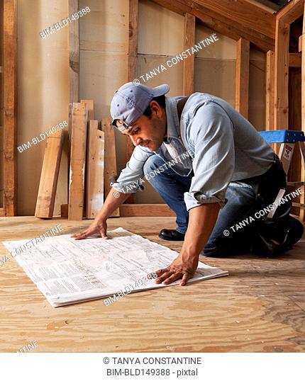 Hispanic construction worker looking at blueprints