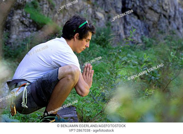 young outdoor sportsman praying in nature, in south of Germany, Bavaria, near border to Austria