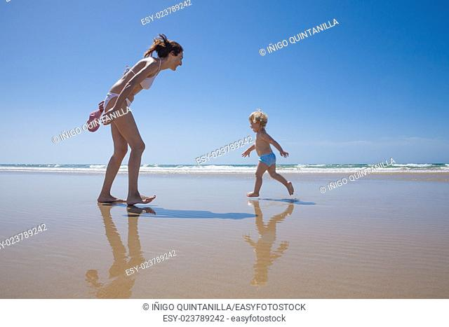 summer family of two years old blonde baby with blue swimsuit running with brunette woman mother in white bikini at sea shore beach sand in Cadiz Andalusia...