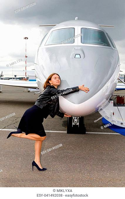 young beautiful woman hugs the nose of the the business jet, sky and clouds through the porthole