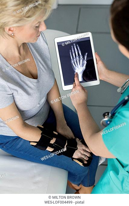 Nurse showing x-ray image on digital tablet to patient
