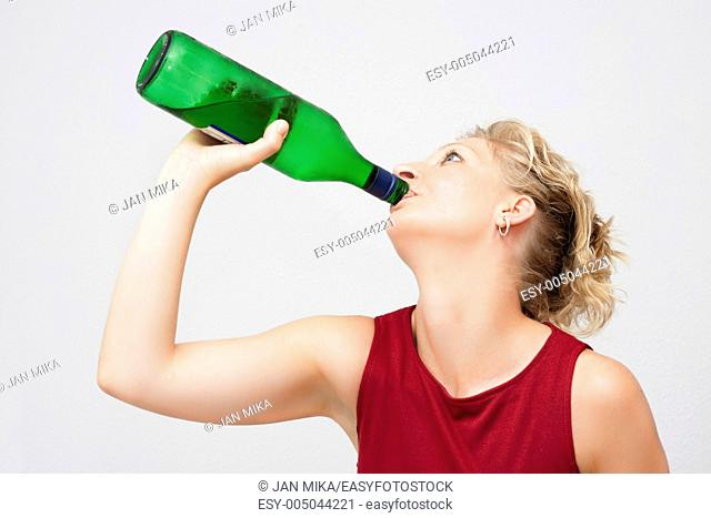Young woman with bottle of alcohol