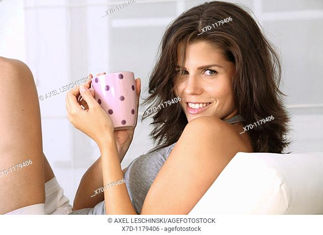 young brunette woman lying on sofa drinking coffee