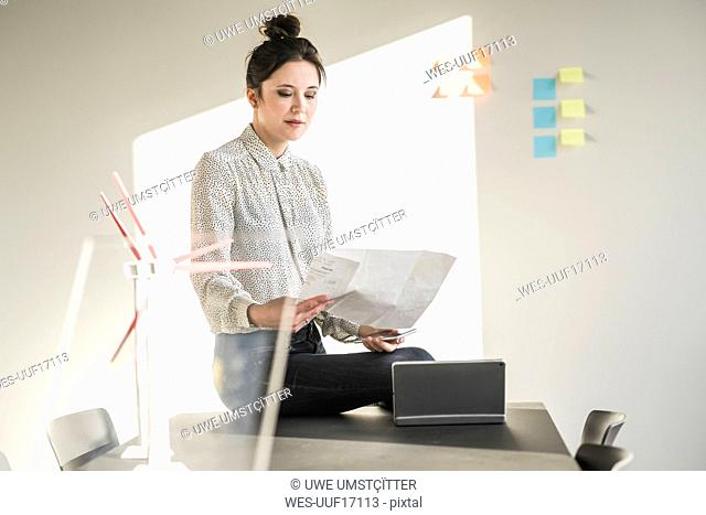 Businesswoman in office reading plan with wind turbine models on desk