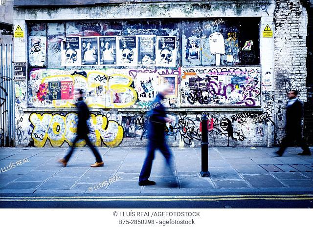 Tres personas irreconocibles andando por la acera de una calle y en la pared de fondo pintada con graffitis. Brick Ln, East End, London, UK, Europa