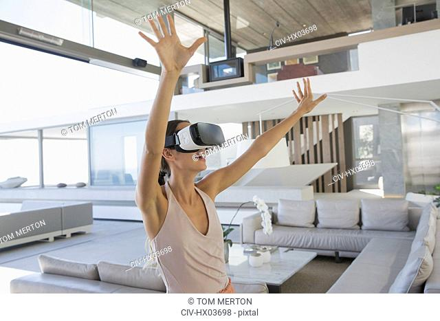 Energetic woman using virtual reality simulator glasses with arms raised in modern, luxury home showcase living room