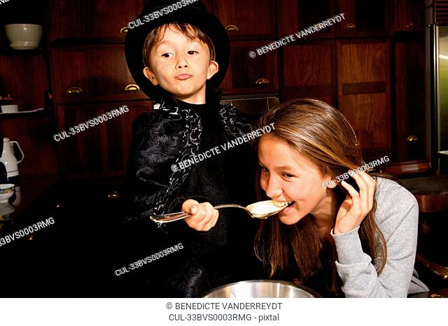 Girl tasting boy magician?s cooking