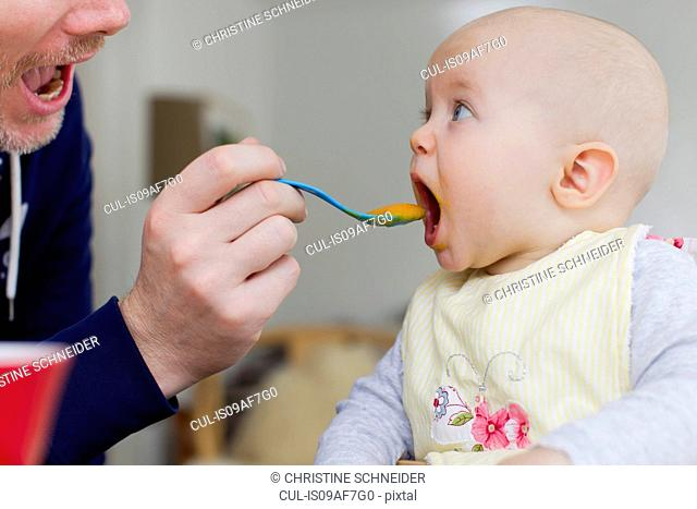 Father spoon feeding baby daughter