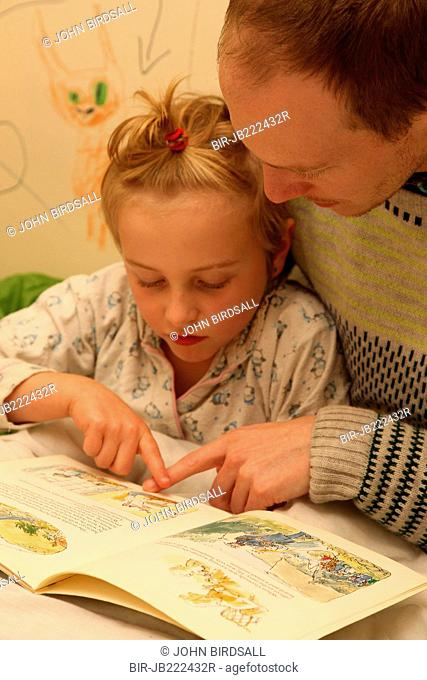 Father reading to daughter at bedtime