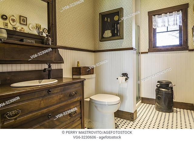 Guest bathroom with antique wooden dresser sink cabinet, toilet, old milk collecting pail inside a LEED certified Country home