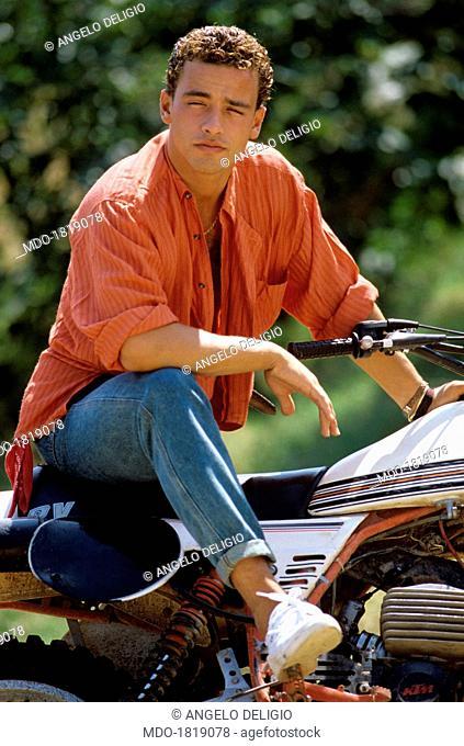 Italian singer-songwriter Eros Ramazzotti sitting on a motorbike. Italy, 1986