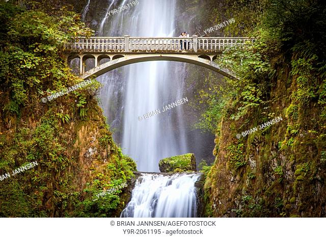 Couple on the footbridge below Multnomah Falls, Columbia River Gorge, Oregon USA