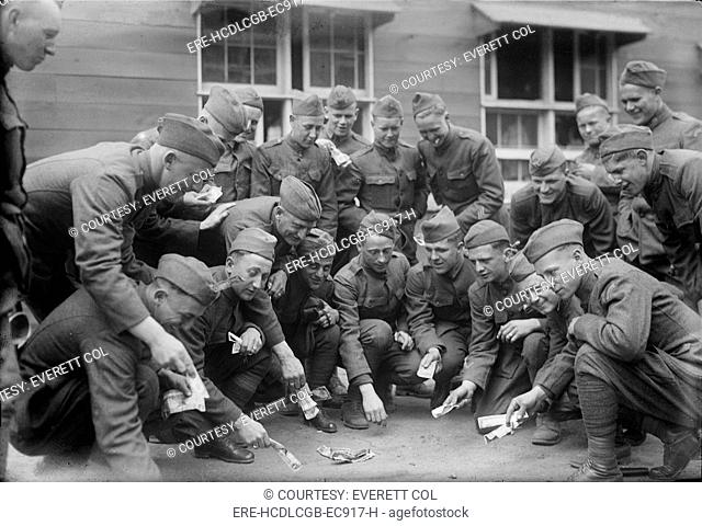 Soldiers playing a dice game, original title: 'Craps at camp', photograph circa 1900s-1930s