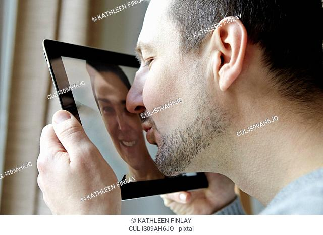 Mid adult man kissing screen of digital tablet