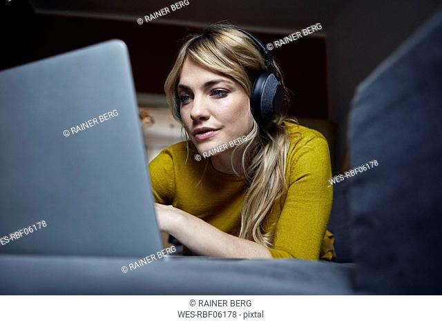 Portrait of woman lying on the couch using headphones and laptop