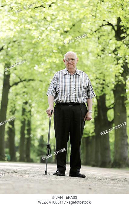Germany, North Rhine Westphalia, Cologne, Portrait of senior man with walking stick in park, smiling