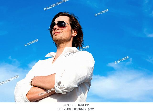 Young man in front of blue sky