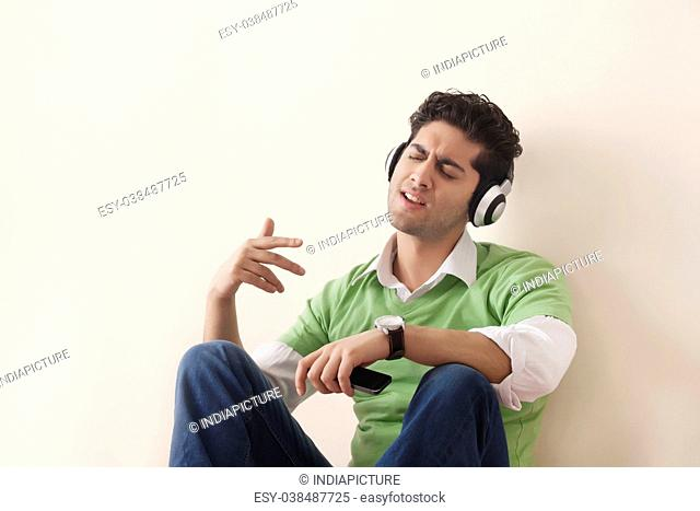 Young man holding phone and listening to music