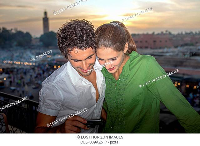 Couple in front of Jemaa el-Fnaa Square looking at smartphone, Marrakesh, Morocco