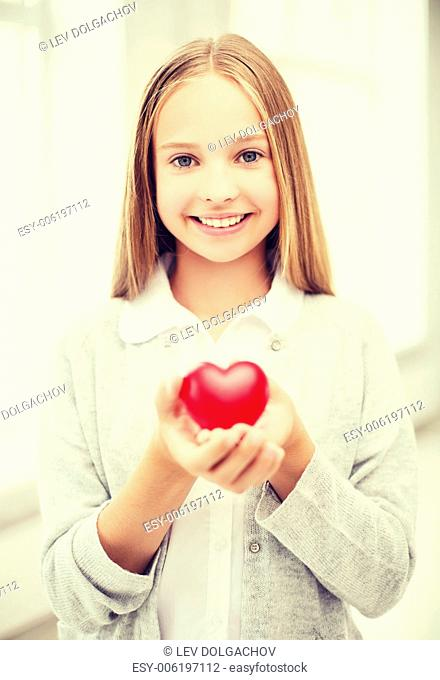 health, charity and beauty concept - beautiful teenage girl showing red heart