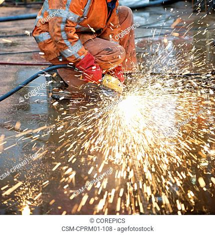 Sparks flying off a grinding machine towards the camera, smoothing the welds on a steel ship deck