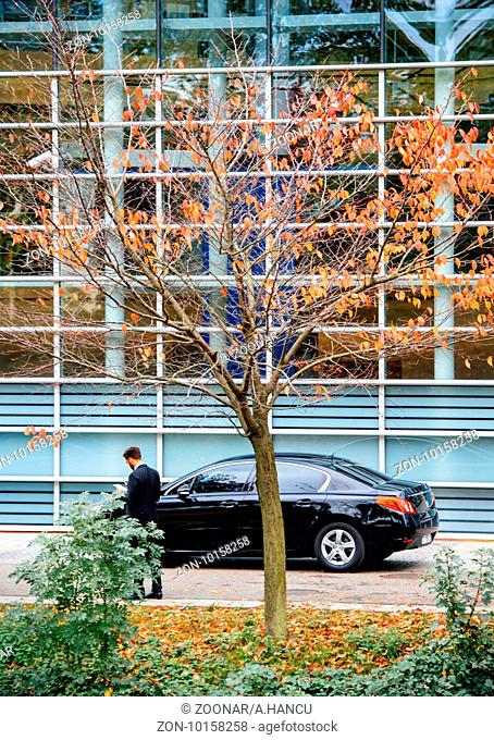 STRASBOURG, FRANCE - OCT 7, 2015: Security guard near his Peugeot car at the rear door of European Parliament building in France during President Francois...