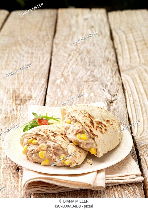 Pita filled with tuna and sweetcorn mayonnaise on whitewashed wood surface